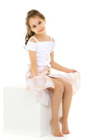 Portrait of Thoughtful Beautiful Girl Sitting on White Cube