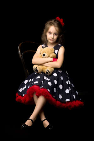 Cute girl in polka dot dress holds a teddy bear