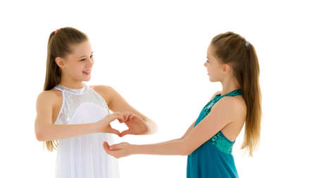 Two adorable girls gymnasts folded palms in the shape of a heart