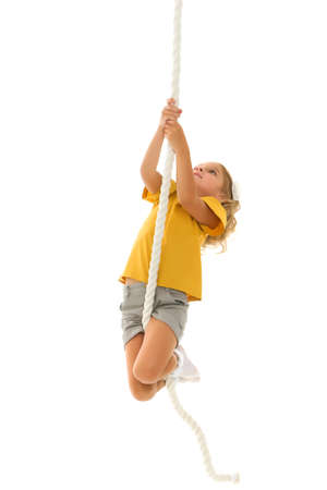 A little girl holds on to the rope with her hands, swinging on it.