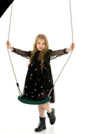 Cute little girl is standing near the swing.