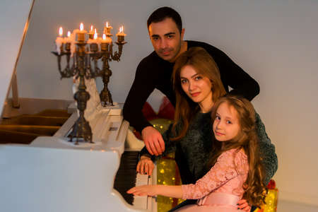 Happy Family Posing near Piano Decorated with Burining Candles