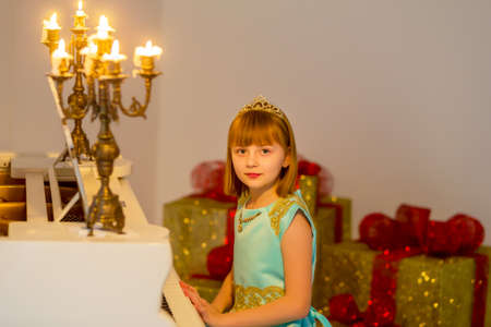 Little girl plays the piano by candlelight.