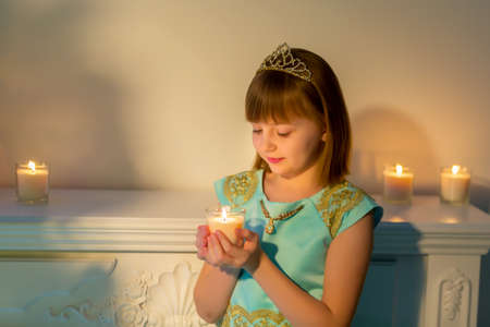 A little girl in a dark room by candlelight.
