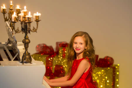 A beautiful girl sits on a classical piano, decorated with burning candles. Zdjęcie Seryjne