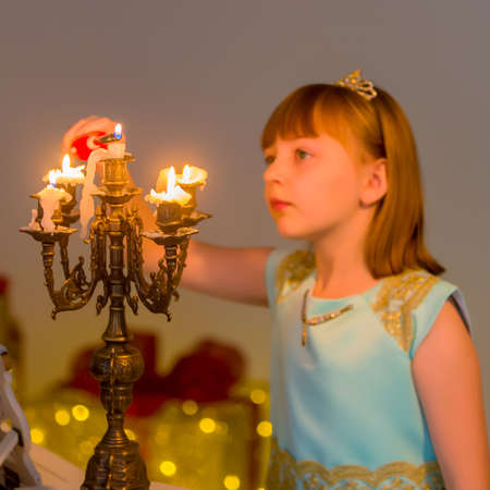 Little girl lights candles on Christmas night.
