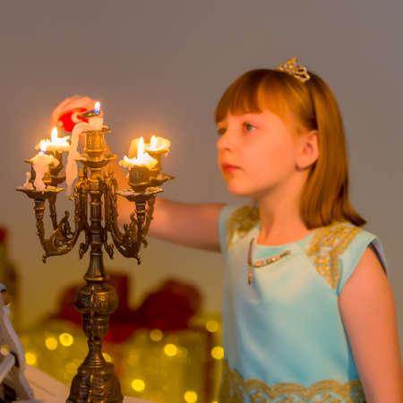 Little girl lights candles on Christmas night.