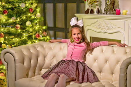 Beautiful little girl sitting on a sofa near the New Year tree. 版權商用圖片