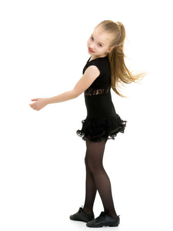 A cheerful little girl is dancing.The concept of a school of dance.