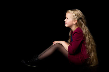 Side view of happy smiling blonde girl. Isolated on black background.