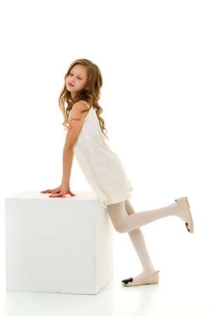 Beautiful Girl in White Dress Standing and Leaning on Cube.