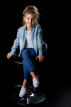 Cute Smiling Blonde Girl Sitting on High Chair in Studio