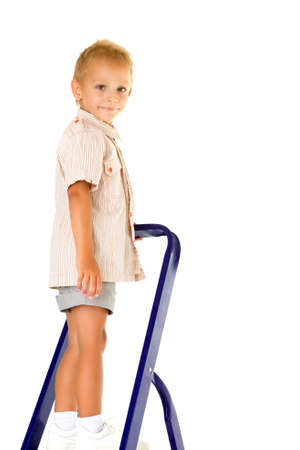 Cheerful little boy climbed a stepladder on the stairs.