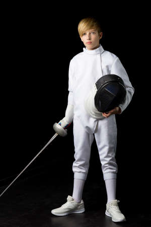 Boy in fencing costume holding mask and sabre