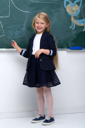 Beautiful schoolgirl standing at blackboard