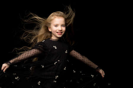 A beautiful little girl stands in the wind, her hair and clothes 스톡 콘텐츠