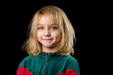 Close up view of a cute smiling little girl posing on black background.