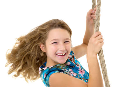 Cute long haired girl sitting on rope swing Reklamní fotografie