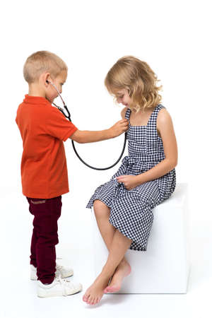 Cute children playing doctor and patient