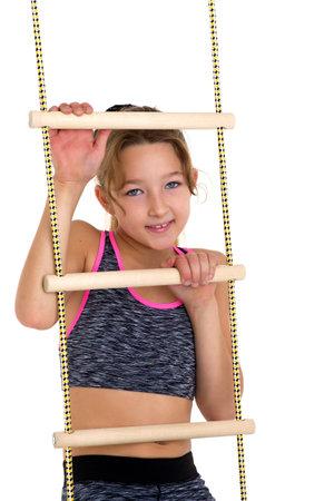 Girl performing gymnastic exercise on rope ladder. Zdjęcie Seryjne