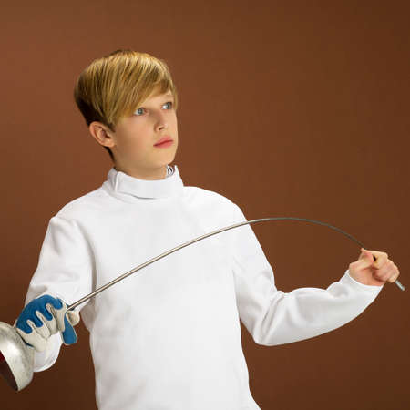 Boy fencer in white fencing costume with rapier