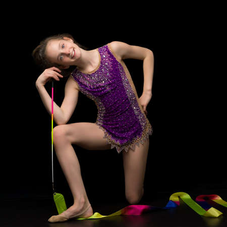 Girl gymnast in the studio on a black background performs gymnastic exercises.