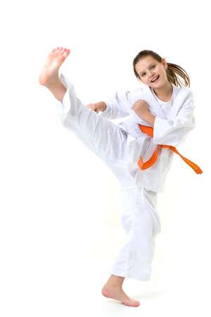 Happy girl in kimono training karate. Photo session in the studio