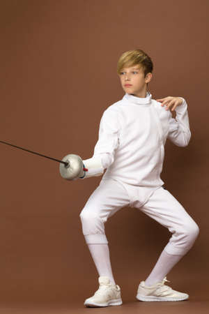 Boy fencer standing in attacking pose Stock Photo