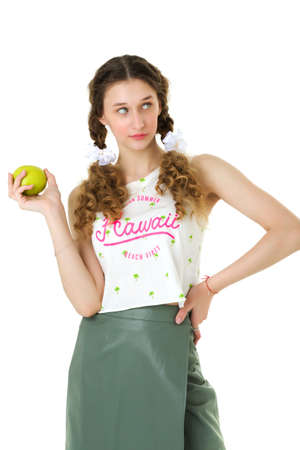 Pretty teen girl in trendy outfit holding apple