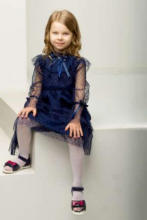 Lovely girl in blue dress sitting on white ladder
