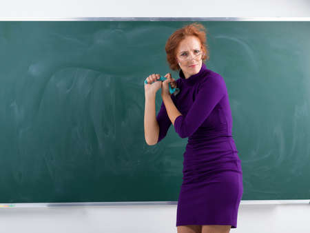 Angry teacher wringing out rag at blackboard