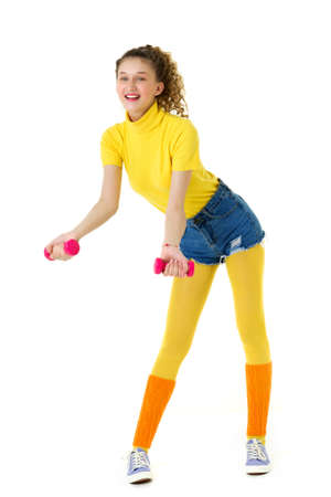 Happy slim girl doing aerobics with red dumbbells
