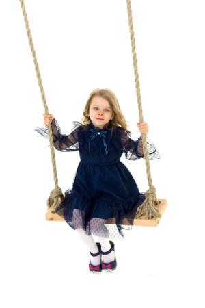 Lovely blonde little girl swinging on rope swing