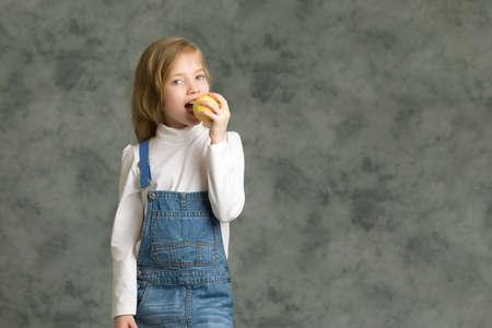 Little girl with apple.Studio portrait. Фото со стока