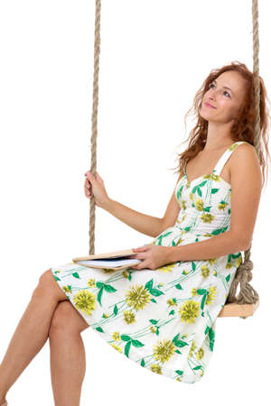 Happy young woman reading book on swing