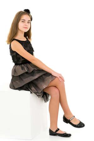 Beautiful Blonde Girl in Elegant Dress Sitting on White Cube