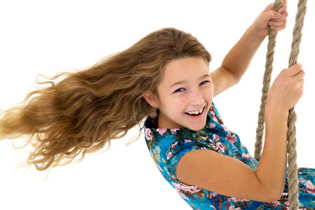 Cute long haired girl sitting on rope swing Фото со стока