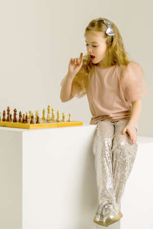 Little girl playing chess.Creative education of a child.