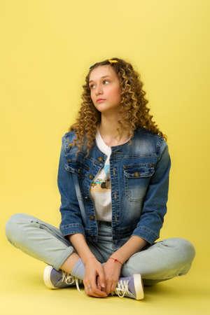 Pretty girl sitting on floor with crossed legs