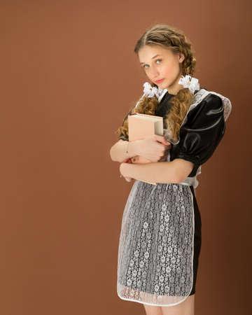 Cheerful girl in school uniform holding close book Фото со стока