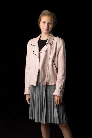 Stylish girl posing against black background