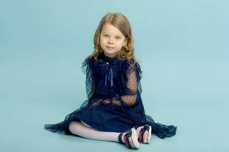 Happy little girl in blue dress sitting on floor