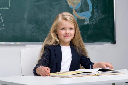 Happy schoolgirl sitting at desk Фото со стока