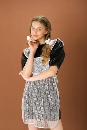 Cheerful blonde teen girl in retro school uniform