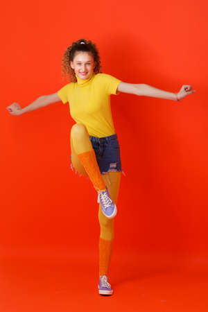 Girl in sports outfit jumping on one leg