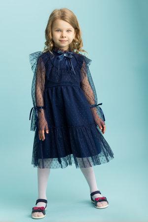 Lovely little girl posing in beautiful blue dress Фото со стока