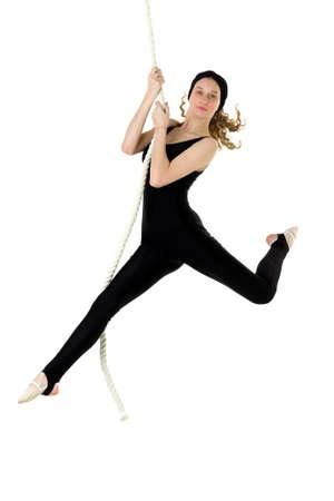 Sports teenage girl hanging on a rope bungee Фото со стока