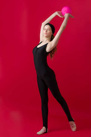Gymnast girl in bodysuit doing exercise with ball