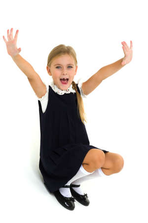 A cheerful blonde in a school uniform is sitting on the floor and waving her hands Фото со стока