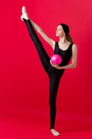 Girl in black bodysuit stretching with pink ball Фото со стока